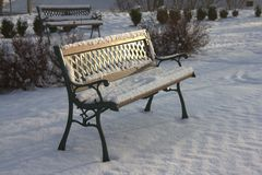 Rest of Nature. Bench covered by the white snow. In the middle of the winter Stock Photo