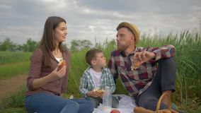 Rest in nature, merry family with child boy chatting while eating bakery at picnic outdoors in green field against sky. Rest in nature, merry family with child stock video