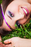 A rest in the park. A portrait of a beautiful brunette model resting on her back in the grass wearing a purple and gold headband and a big smile stock photography