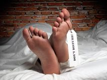 Rest in peace. Funny image of a man who is resting covered with a sheet like in the morgue, with a label on his thumb Royalty Free Stock Image