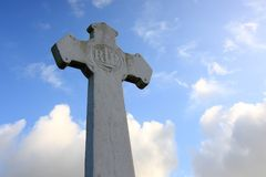 Rest in peace. White tombstone-cross, against cloudy blue sky Royalty Free Stock Images