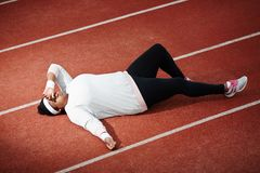 Rest on racetrack. Exhausted over-sized young woman in activewear lying on racetrack after hard training Royalty Free Stock Photo