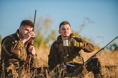 Rest for real men concept. Hunters with rifles relaxing in nature environment. Hunters friends enjoy leisure. Hunting. With friends hobby leisure. Hunters stock image