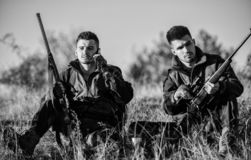Rest for real men concept. Hunters with rifles relaxing in nature environment. Hunting with friends hobby leisure. Hunters satisfied with catch drink warming stock photography