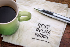 Rest, relax, enjoy on napkin. Rest, relax, enjoy - handwriting on a napkin with a cup of coffee Royalty Free Stock Photo