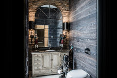 In the rest room are antique mirror and vintage wall sconces. Stock Images
