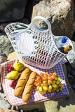 Rest by the sea with grapes, apples, pears, baguettes, wine and a basket on the coverlet Stock Photos