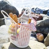 Rest by the sea with grapes, apples, pears, baguettes, wine and a basket on the coverlet Stock Image