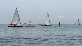 Rest on sea. Sea kayak, boats with sail, catamaran, stand up paddler. Outdoor sea sporting activity. Sea landscape Stock Image
