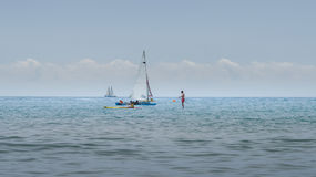 Rest on sea. Sea kayak, boats with sail, stand up paddler. Outdoor sea sporting activity. Sea landscape Royalty Free Stock Images