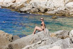 Rest by the sea. Seascape with tanned blond woman in bikini. Rest by the sea. Seascape with short-haired tanned blond woman in black bikini and tinted sunglasses royalty free stock photo