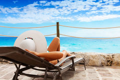 Rest on the seaside. Beautiful woman laying on the sun chair near the sea Stock Photo