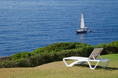 Rest on the shore. Chaise lounge in a lonely place on the coast overlooking the sea and the yacht stock images