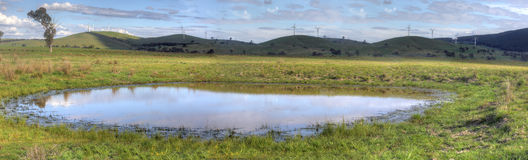 Rest for the soul at the watering hole. Rural views of picturesque countryside, rolling hills and eco-friendly wind farm and a foreground watering hole Stock Photo