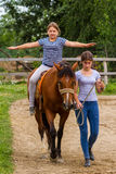 Rest in the summer children`s equestrian camp in Ukraine. Vynohradiv, Ukraine - July 12, 2017: Girls learn horseback riding during a vacation in the summer stock image