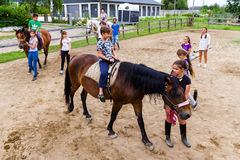 Rest in the summer children`s equestrian camp in Ukraine. Vynohradiv, Ukraine - July 12, 2017: Children learn to ride a horse during a vacation in the summer royalty free stock images