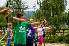 Rest in the summer children`s equestrian camp in Ukraine. Vynohradiv, Ukraine - July 12, 2017: Children learn to shoot arrows during a vacation in the summer stock images