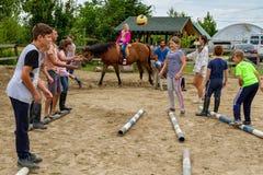 Rest in the summer children`s equestrian camp in Ukraine. Vynohradiv, Ukraine - July 12, 2017: Children play during the vacation in the summer children`s Stock Image