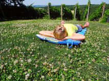 Rest on a summer meadow. The girl in the meadow of clover beside a vineyard royalty free stock image