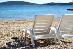 Rest, summer relaxation and sunbathing concept. Two white plastic beach chairs on the white beach near turquoise piercing blue sea in the sunshine. Beach chaise stock image