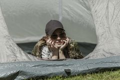 Rest in tent. The girl looks out of tent and has a rest Stock Photo