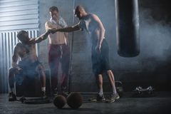 Rest three guys who have completed a complex. Crossfit workout in the gym Royalty Free Stock Photos