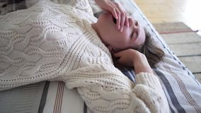 Rest time after a hard day's work - caucasian girl in a beautiful comfortable white sweater knitted from wool regains. Strength on the bed 4k stock footage