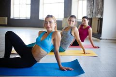 Group of women rest on mats between exercise sets. Rest time, interval workout, activity, healthy lifestyle, sport, weight loss, tabata. Group of women respite stock photo