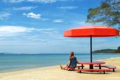 Rest unter einem Rot des Strandschirms lizenzfreie stockfotos
