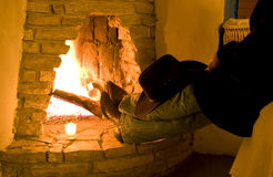 Rest and Warmth. A person sitting with their boots resting on the hearth of a blazing rustic fireplace stock photos