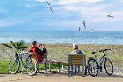 Rest after weekend bike trip - a couple sit on deckchairs and en. Joy a beautiful view of the sea and seagulls, making photo on the smartphone Stock Photos
