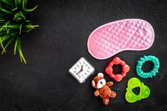 Rest for young mother concept. Sleep mask, plant, alarm clock, toys on black background top view copyspace. Rest for young mother concept. Sleep mask, plant Stock Image