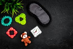 Rest for young mother concept. Sleep mask, plant, alarm clock, toys on black background top view copyspace. Rest for young mother concept. Sleep mask, plant Royalty Free Stock Photography