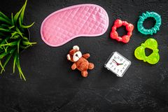 Rest for young mother concept. Sleep mask, plant, alarm clock, toys on black background top view copyspace. Rest for young mother concept. Sleep mask, plant Royalty Free Stock Photo