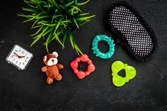 Rest for young mother concept. Sleep mask, plant, alarm clock, toys on white background top view.  Stock Photos