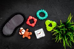 Rest for young mother concept. Sleep mask, plant, alarm clock, toys on white background top view.  Stock Image