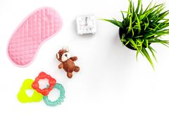 Rest for young mother concept. Sleep mask, plant, alarm clock, toys on white background top view copyspace. Rest for young mother concept. Sleep mask, plant Royalty Free Stock Photos