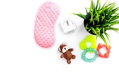 Rest for young mother concept. Sleep mask, plant, alarm clock, toys on white background top view copyspace. Rest for young mother concept. Sleep mask, plant Royalty Free Stock Photo