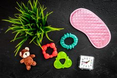 Rest for young mother concept. Sleep mask, plant, alarm clock, toys on white background top view.  Royalty Free Stock Photography