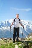 Restare turistico maturo su una scogliera in alpi Fotografie Stock