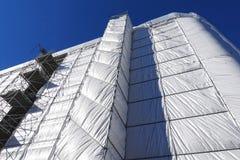 Restauração da construção, a construção coberta com um encerado cinzento fotos de stock