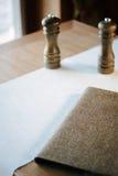 Restauracja stół z menu książką, tablecloth i solankowymi potrząsaczami, Obrazy Royalty Free