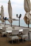 Restauracja stoły, krzesła i fałdowi parasole przy nadmorski na chmurnym dniu, Zdjęcia Royalty Free