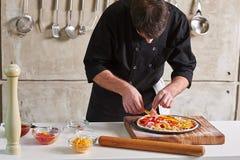 Restauracyjnej hotelowej intymnej szefa kuchni narządzania pizzy sumujące polewy Zdjęcia Stock