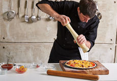 Restauracyjnej hotelowej intymnej szefa kuchni narządzania pizzy sumujące polewy Zdjęcie Stock