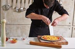 Restauracyjnej hotelowej intymnej szefa kuchni narządzania pizzy sumujące polewy Zdjęcia Royalty Free