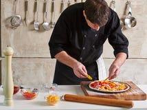 Restauracyjnej hotelowej intymnej szefa kuchni narządzania pizzy sumujące polewy Fotografia Royalty Free