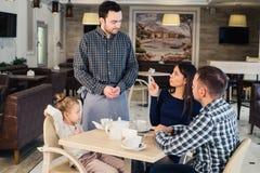 Restauracyjny i wakacyjny pojęcie - kelner daje menu szczęśliwa rodzina przy kawiarnią Obrazy Stock