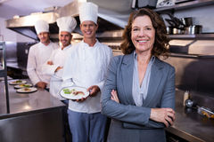 Restauracyjny kierownik pozuje przed drużyną szefowie kuchni Obrazy Stock
