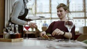 Restauracyjny poj?cie: tylko r?ki, us?uga i naczynie, Kelner przynosi rozkaz wo?owiny stek, m??czyzny siedz?cy mienie w r?kach zbiory